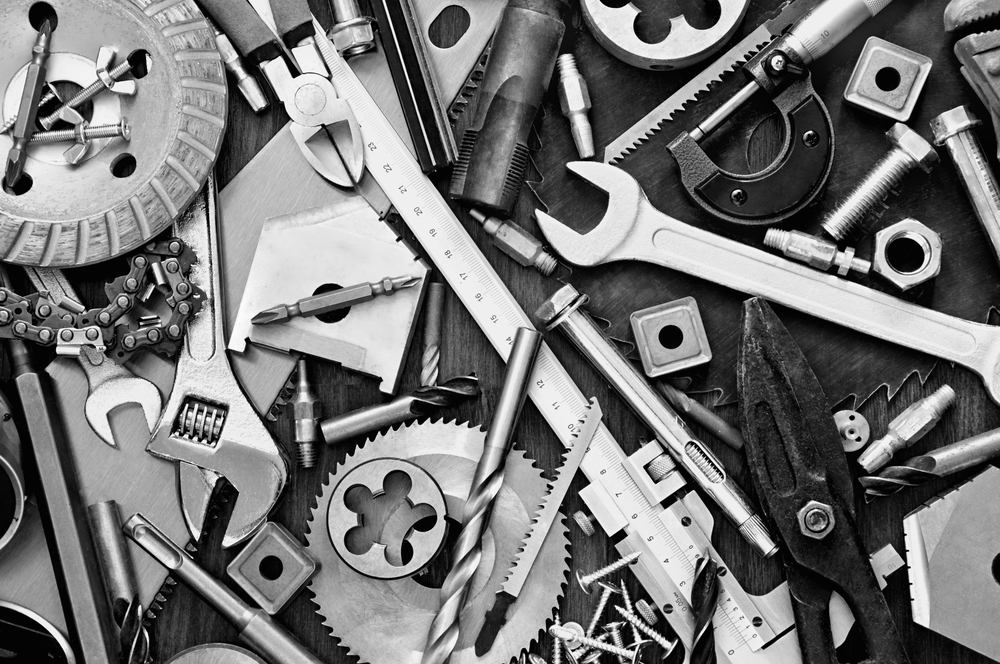 Collection of tools including spanners, screws, drill and saw parts